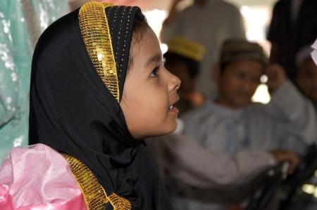 A Burmese girl watches a performance.